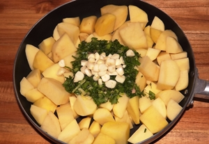 Добавляем в сковородку масло, картошку, укроп и чеснок