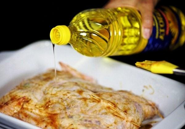 Поливаем фаршированную  курицу постным маслом