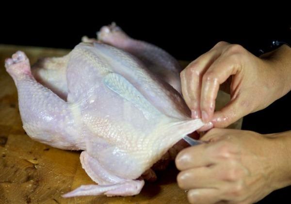 Ложкой отделяем кожу вокруг туловища курицы