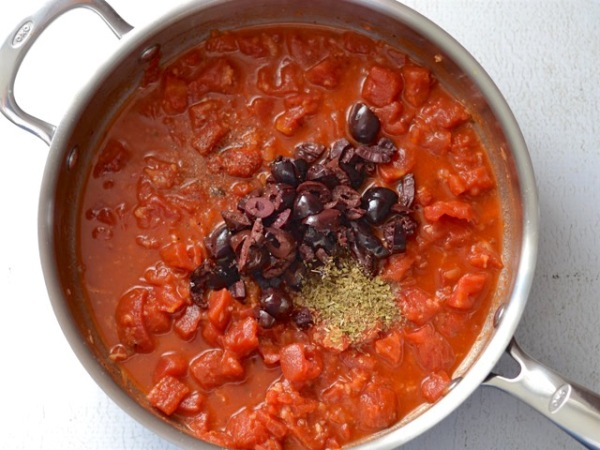 Добавляем в сотейник помидоры, оливки и специи