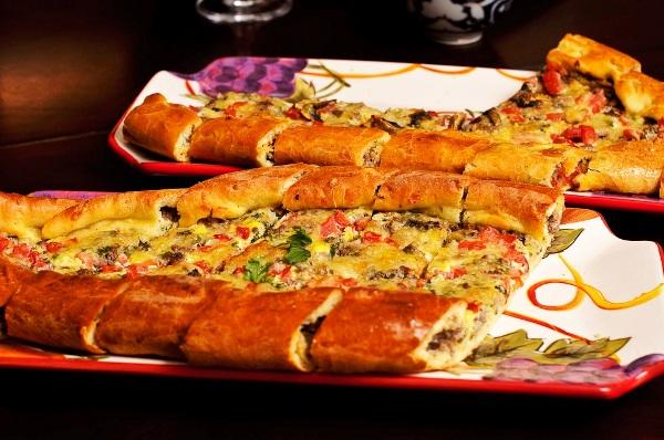 Готовую турецкую пиццу пиде нарезаем кусочками
