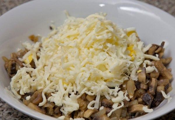 Добавляем в миску поджарку из грибов, сыр и яйца