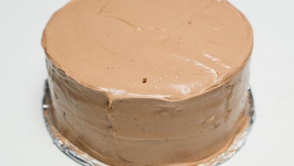 Покрываем ореховый торт кремом сверху и с боков